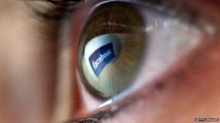 A Facebook logo is reflected in a human eye.