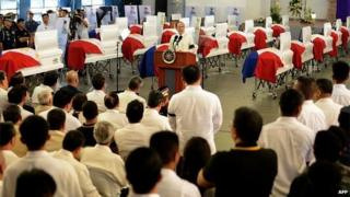 Philippine President Benigno Aquino gives a message in front of the coffins of police commandos killed in a botched anti-terror operation during a necrological service at the Camp Bagong Diwa, in Manila on January 30, 2015.