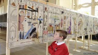 Boy standing in front of Great Tapestry of Scotland