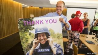 Peter Greste's brother Peter holds a poster of his brother as he celebrates the journalist's release at a press conference in Brisbane