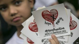 A child holds stickers of a campaign to save two Australian citizens from death sentence, in Bali, Indonesia, 31 January 2015.
