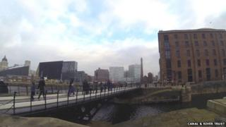 People walking over canal at Liverpool Albert Docks
