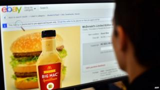 Photo illustration of a woman in Sydney looking at a webpage of eBay offering bids for fast-food giant McDonald's Big Mac special sauce.