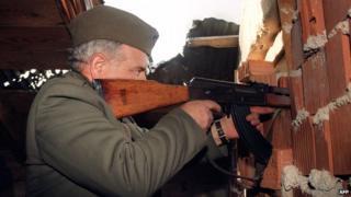 A Serb fighter fires his machine gun at a Croatian force (1993)