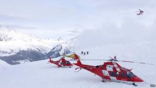 Helicopters land at the site of an avalanche that hit nine skiers on 31 January