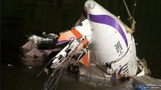 Rescuers lift the wreckage of the TransAsia ATR 72-600 out of the Keelung river at New Taipei City
