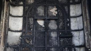 A burnt crucifix stands at the altar of St Sebastian's Church after a fire destroyed the church on Monday, in New Delhi, India, Tuesday, Dec. 2, 2014.