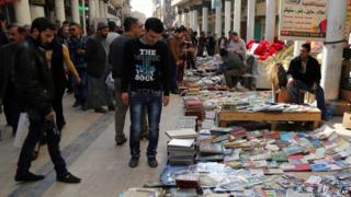 Iraqis look at books on al-Mutanabi Street, home to the city's book market in central Baghdad, 23 January 2015