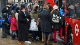 Commuters queue to get onto a bus outside Vauxhall bus station