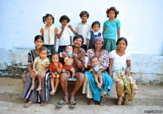 Vadthya Sukhya and Vadthya Achi pose with their eleven children in front of their home in Nalgonda District, some 150 kilometers from Hyderabad on October 21, 2011