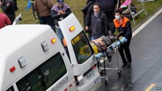 Rescue personnel put an injured passenger from a TransAsia flight that crash-landed into a river outside Taiwan's capital Taipei into an ambulance