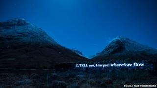 Words of poem beamed on to a dyke in Glencoe