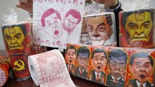 Rolls of toilet paper and packages of tissue paper printed with images of Hong Kong Chief Executive CY Leung are shown by Hong Kong Democratic Party Vice Chairman Lo Kin-hei at his office in Hong Kong, 7 February 2015