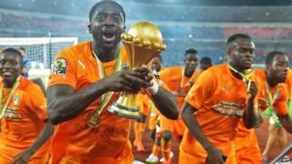 Ivory Coast's defender Kolo Toure raises the trophy as he celebrates after winning the 2015 African Cup of Nations