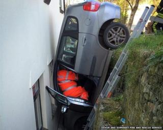 Car trapped between house and wall