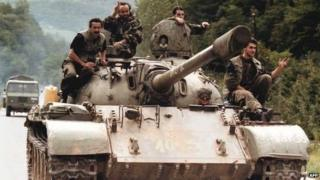 An archive photo of Bosnian-Serb soldiers on a T-55 tank in 1995