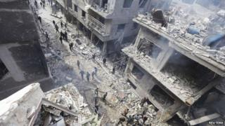 People inspect a site hit by what activists said were airstrikes by forces loyal to Syria's President Bashar al-Assad in the Douma neighborhood of Damascus