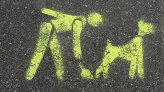 A stencil of a man scooping up dog mess