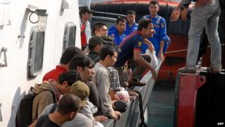 A group of Pakistani and Afghan asylum seekers arrive aboard an Indonesian maritime police boat in the port of Banten, in western Java island on October 9, 2012