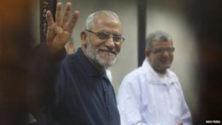 """Mohammed Badie (L) flashes the """"Rabaa"""" sign at a trial at the police academy on the outskirts of Cairo (14 December 2014)"""