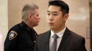 New York City police officer Peter Liang, right, leaves the courtroom after his arraignment at Brooklyn Superior court on 11 February 2015