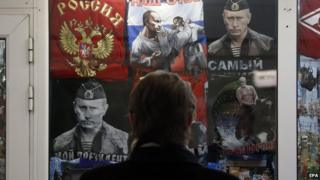 Pass-by looks at Moscow shop selling t-shirts featuring pictures of President Putin 11/02/2015