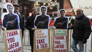 Protesters with posters of Iranian director Jafar Panahi outside the Berlin film festival draw attention to his travel ban as his film Taxi premieres there 06/02/2015