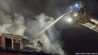 Firefighters on a platform using a water jet to extinguish a fire in a roof