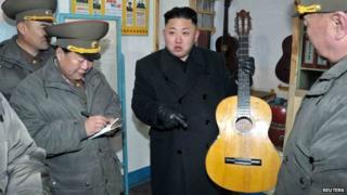 North Korean leader Kim Jong-Un (C) holds a guitar during his visit to a military unit on the Wolnae Islet Defence Detachment in the western sector of the front line, which is near Baengnyeong Island of South Korea 12 March 2013.
