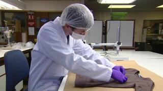 A forensic scientist test material in a lab