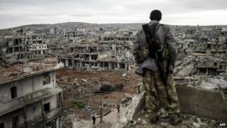 A Kurdish fighter surveys the devastation in Kobane (30 January 2015)