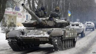 A column of Ukrainian forces vehicles drive in a convoy in Volnovakha city, Ukraine, 18 January 2015