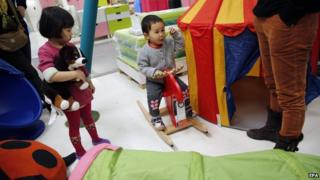 File picture of two children playing in a furniture shop in Beijing
