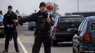 A German policeman stops vehicles near the Polish border on 15 April 15 2014