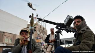 Houthi militia stand watch over a rally celebrating the Houthis takeover in Sanaa on 11 February