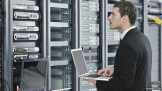 Office worker in network server room