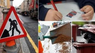 Traffic sign, child writing, road being dug up, and bins waiting to be emptied.