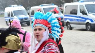 Would-be revellers stand in front of police cars in Braunschweig, Germany, on Sunday after police in the northern German city cancelled the annual carnival procession shortly before it was due to begin over fears of a terrorist attack