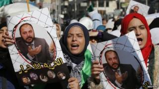 Protesters from the Islamic Action Front, carry pictures of the deputy overall leader of Jordanian Muslim Brotherhood Zaki Bani Rsheid during a demostration to show their solidarity with Palestinians and anger at the political arrest, after the Friday prayer in Amman November 28, 2014