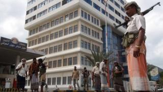 Members of the Popular Resistance Committees (PRC) stand guard outside the television building in Aden, Yemen (16 February 2015)