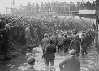 February 1928: Crowds watch the annual Shrovetide football game, which is 'kicked - off' in the stream which runs through the Derbyshire town of Ashbourne