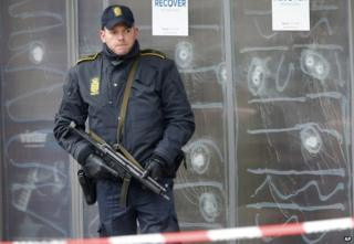 A police officer stands in front of the cultural centre where a gunman killed one person in Copenhagen, Denmark. 16 February 2015