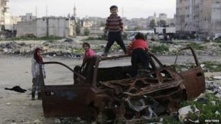 Syrian children play in the wreckage of a car in Aleppo's al-Myassar district (16 February 2015)
