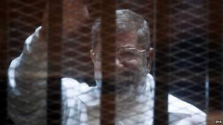 Mohammed Morsi sits in a defendants' cage in a courtroom in Cairo (15 February 2015)