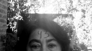 A woman with 43 painted on her forehead to show support for the 43 missing students in Mexico