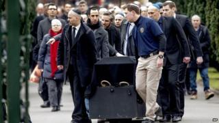 The coffin of Dan Uzan who was killed in one of Sunday's attacks in Copenhagen is brought out after the funeral at the Mosaic Cemetery, in Copenhagen on Wednesday Feb. 18, 2015