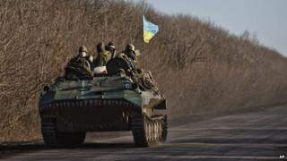 Ukrainian troops ride on an armoured vehicle outside Artemivsk, Ukraine, after pulling out of Debaltseve - 18 February 2015