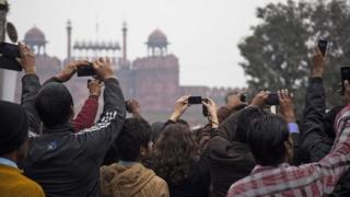 Indians hold up their mobile phone as the Republic Day parade marches past in front of the historical Red Fort in Delhi on Jan. 26, 2015.