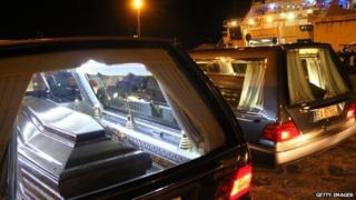The coffins with the bodies of immigrants who died trying to reach the Italian coast arrive from Lampedusa on 11 February 2015