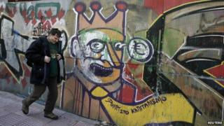 A man walks next to graffiti depicting a clown with a euro sign popping from his eye, in Athens 19 February 2015